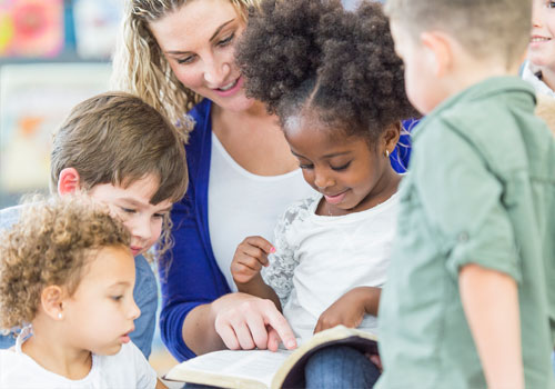 A young woman teaches young children from the Bible