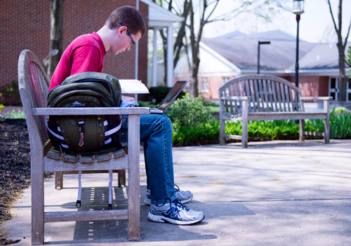 A student studies on a bench on the LBC Lancaster Campus
